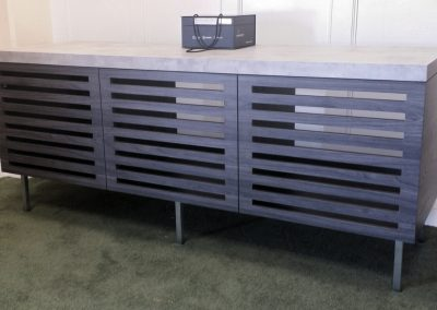 Contemporary equipment cabinet, faux concrete counter and textured wood body, slates provide air flow