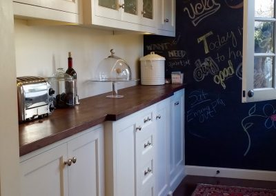 Entry from back door leads through butlers pantry into kitchen.  Chalk board wall makes a place for fun messaging!